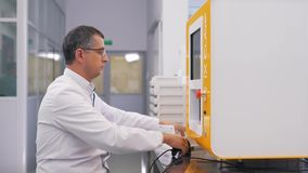 Техник лаборатории просматривает трубки в лаборатории акции видеоматериалы