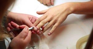 Техник ногтя извлекая надкожицы от ногтей клиентов видеоматериал