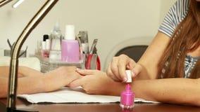 Техник ногтя прикладывая лак для ногтей к ногтям клиентов сток-видео