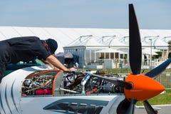 Техник проверяет тренировку двигателя турбовинтового самолета двухместную и пилотажные воздушные судн Grob g 120TP низко-крыла стоковая фотография rf