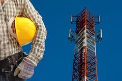 Техник против башни радиосвязи, покрашенной белизны и re стоковое изображение rf