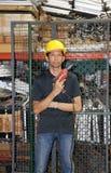 Техник с желтым положением шлема и бурильщик в руке в рабочей зоне стоковое фото