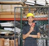 Техник с желтым положением шлема и бурильщик в руке в рабочей зоне стоковые фото