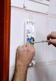 Техник устанавливая новый телефон внутренной связи внутри дома Стоковые Изображения RF