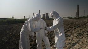 Техническая команда работников лаборатории в hazmat одевает почва забора и рассматривать вегетация и от поля близко электростанци видеоматериал