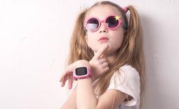Технология для детей: девушка нося розовые стекла использует smartwatch стоковые изображения rf
