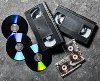 Технология развлечений и средств массовой информации от 90's CD& x27; s, магнитофонные кассеты, видео- кассеты на черной конкретн Стоковые Фотографии RF
