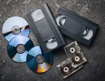 Технология развлечений и средств массовой информации от 90's CD& x27; s, магнитофонные кассеты, видео- кассеты на черной конкретн Стоковое Изображение