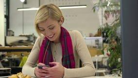 технология Усмехаясь женщина используя мобильный телефон в кафе внутри помещения акции видеоматериалы