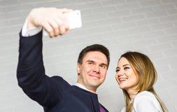 Технология, фотографировать, и бизнесмены концепции - счастливых работников офиса делая selfie внутри помещения Стоковое Изображение RF
