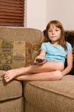Телевидение молодого женского ребенка ослабляя и наблюдая Стоковые Фото
