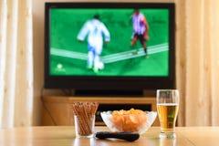 Телевидение, ТВ смотря (футбол, футбольный матч) с lyi закусок стоковые фотографии rf