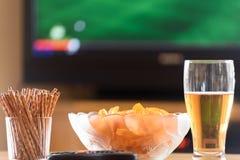 Телевидение, ТВ смотря (футбол, футбольный матч) с lyi закусок стоковое фото