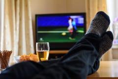 Телевидение, ТВ смотря (футбольный матч) с ногами на таблице и стоковые фото