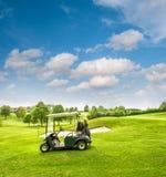 Тележка гольфа на поле для гольфа голубое пасмурное небо зеленого цвета поля стоковые фотографии rf