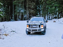 тележка 4x4 перемещаясь на дорогу снега зимы в лесе Стоковое Изображение