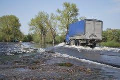Тележка путешествует через реку которое пришло из своих банков и f стоковые изображения