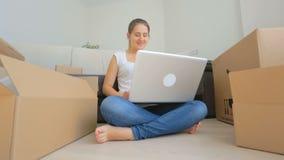 Тележка сняла счастливой молодой женщины двигая к новому дому и используя цифровую таблетку сток-видео
