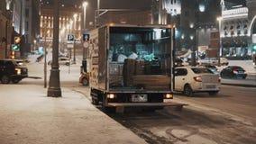 Тележка с открытым хоботом на стороне дороги на городе зимы ночи видеоматериал
