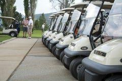 Тележки гольфа в линии ждать для того чтобы управляться стоковое фото