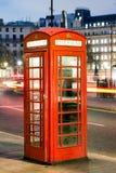 Телефонная будка Лондона на ноче с течь фары корабля Стоковые Изображения RF