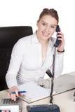 Телефоны молодой женщины на столе стоковое изображение