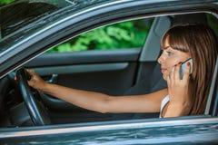 Телефон автомобиля молодой женщины сидя говоря Стоковое Фото