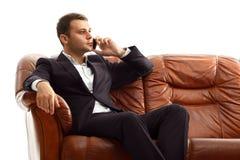 Телефон бизнесмена говоря сидя на кресле Стоковые Фото
