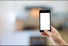 телефон владением руки принимает комнату кухни фото стоковое изображение