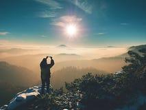 Телефон владением Hiker над головой, фотографирует туманный ландшафт зимы Стоковая Фотография