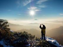 Телефон владением Hiker над головой, фотографирует туманный ландшафт зимы Стоковые Изображения RF