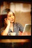 Телефон женщины Азии говоря в кафе и наслаждаться кофе Стоковые Изображения