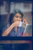 Телефон женщины Азии говоря в кафе и наслаждаться кофе Стоковое Изображение