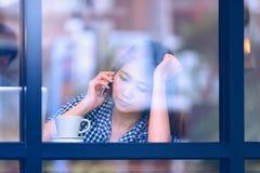 Телефон женщины Азии говоря в кафе и наслаждаться кофе Стоковые Фотографии RF