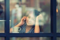 Телефон женщины улыбки Азии говоря в кафе и наслаждаться кофе Стоковые Изображения