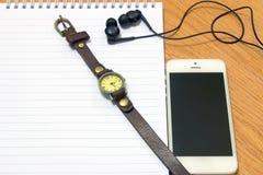 Телефон и наушники вахты на блокноте стоковое изображение rf