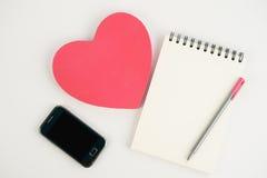 Телефон и тетрадь подарочной коробки сердца на белой предпосылке Стоковое Изображение