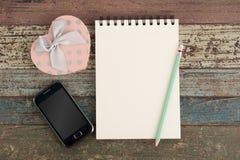 Телефон и тетрадь подарочной коробки сердца на деревянной предпосылке таблицы Стоковые Изображения