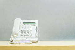 Телефон крупного плана белый, телефон офиса на запачканном деревянном столе и стена матированного стекла текстурировали предпосыл Стоковое Фото