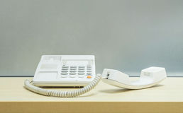 Телефон крупного плана белый, телефон офиса на запачканном деревянном столе и стена матированного стекла текстурировали предпосыл Стоковые Фото