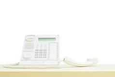 Телефон крупного плана белый, телефон офиса на запачканном деревянном столе в конференц-зале под светом окна изолированным на бел Стоковое Фото