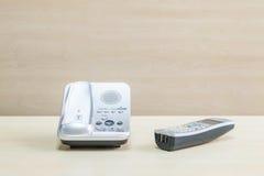 Телефон крупного плана серый, телефон офиса на запачканном деревянном столе и стена текстурировали предпосылку в конференц-зале п Стоковые Изображения