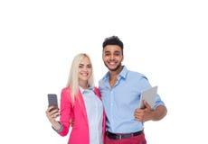 Телефон клетки планшета владением обнимать красивой молодой счастливой влюбленности пар усмехаясь умный, испанская улыбка женщины стоковые фото
