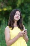 телефон обнесенное решеткой места в суде девушки 14 год и смотреть вверх задумчиво Стоковые Изображения