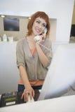 Телефон парикмахера отвечая на приемной стоковая фотография