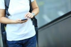 Телефон пользы скейтбордиста молодой женщины умный в эскалаторе города Стоковое Фото