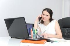 Телефон привлекательной пользы бизнес-леди умный и сидеть на ее wor стоковые фотографии rf