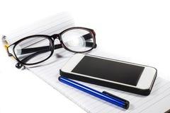 Телефон ручки тетради стекел стоковые фото