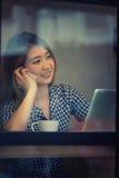 Телефон счастливой женщины Азии говоря в кафе и наслаждаться кофе Стоковое Фото