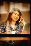 Телефон счастливой женщины Азии говоря в кафе и наслаждаться кофе Стоковые Изображения RF